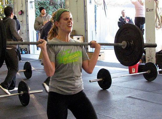 Cindy holds the barbell at the top of a hang power clean