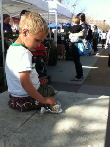 Luke eats his taco at the Triangle Farmers Market