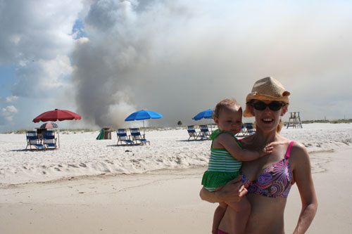Madeline and Cindy stand on the shore at Orange Beach while a wildfire sends up a huge plume of smoke in the background.
