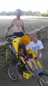 Andy sitting on a wall, while Luke stands next to Mads in the yellow jogging stroller.