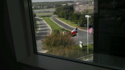 Photo shows view looking outside at roads and flag poles