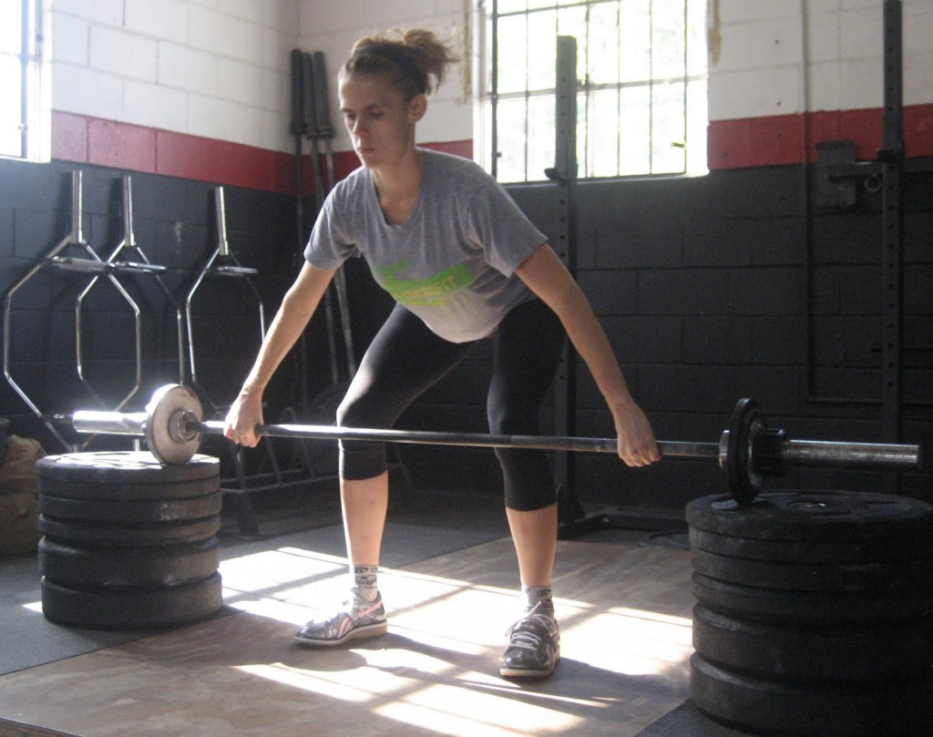 Cindy stands behind a barbell with back bent and hands in a wide grip.