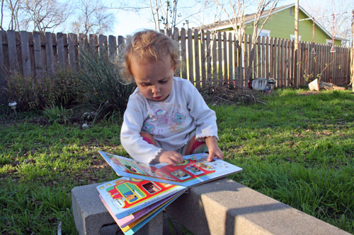 Child squats while reading book
