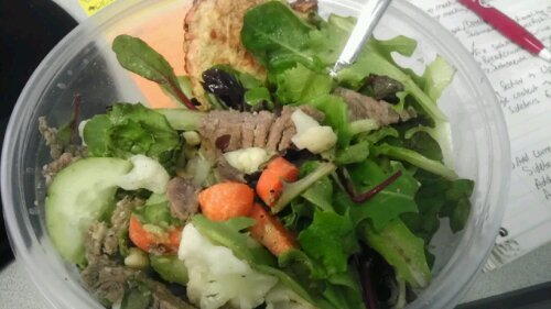 Fork in plastic bowl of greens, carrots, cucumbers and meat