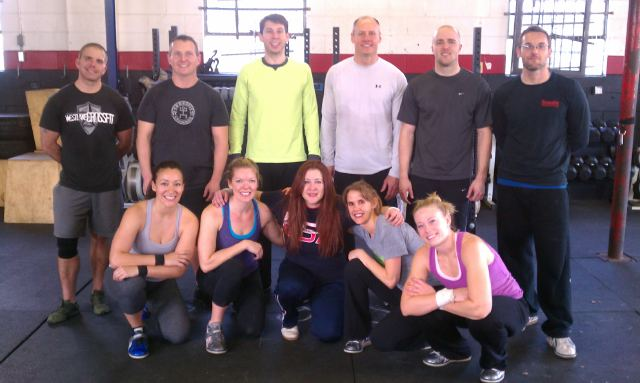 Group of 11 people posing at gym