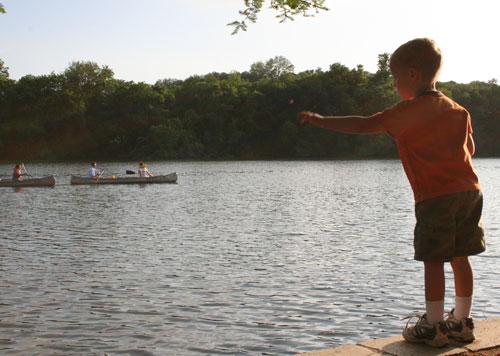 Luke throws a rock in the lake