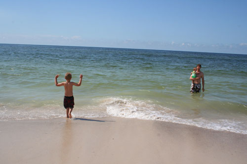 Luke runs toward the shallow waves of the Gulf of Mexico